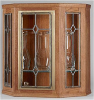 "Ambry - Clear leaded beveled glass in door and two side panels. Made of Oak Plywood with light finish. Adjustable glass shelf inside. Size: 25""H x 24-1/2""W and 10-1/2""D. Lighted interior"