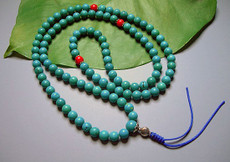 Turquoise 111 bead mala with three coral accents and knotted tassel.