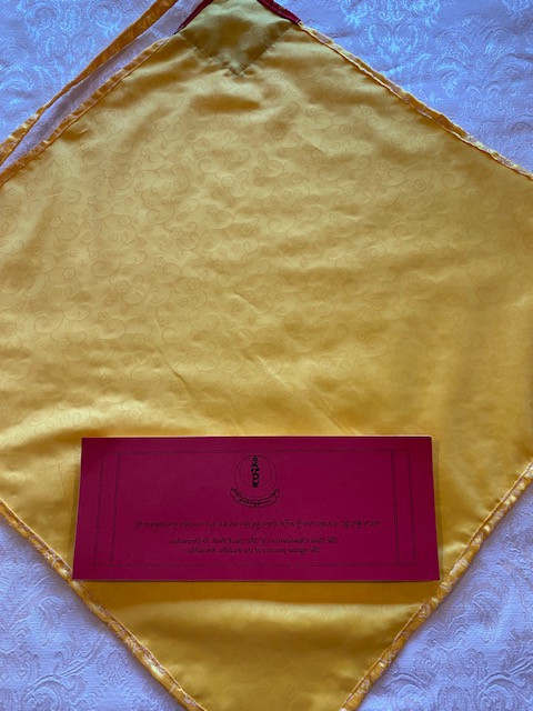 Yellow with red accent pecha text cover with tie closure,  open position