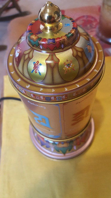 Love and compassion electric prayer wheel with Om Mani Padme Hum and other mantra, top view with seed syllables.